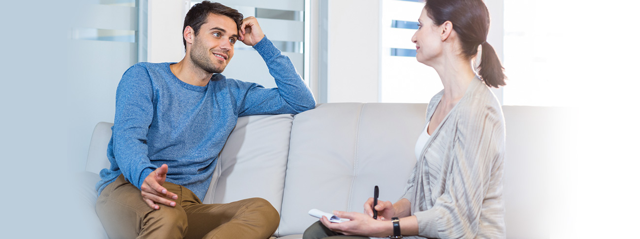 A man in a blue sweater sits on a white couch facing a woman in a grey sweater. They appear to be having a conversation.
